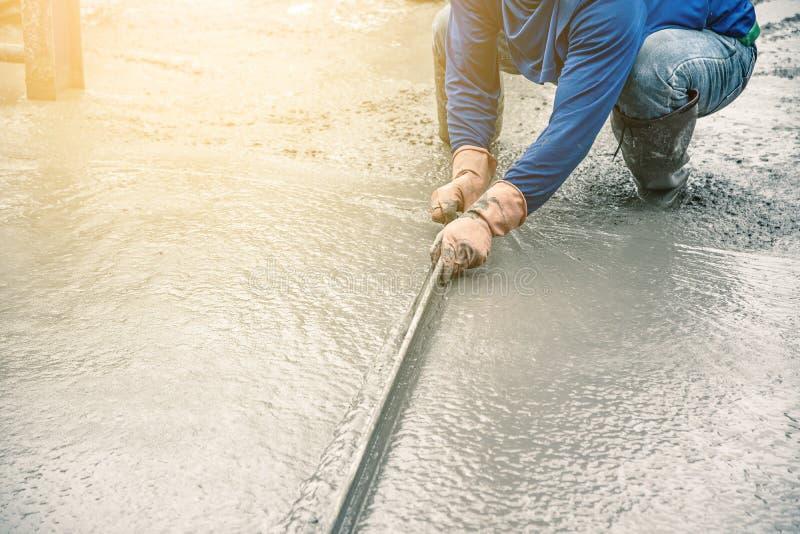 Sentada del hombre del trabajador y usar una espátula de madera para el cemento después de verter el hormigón preparado imagenes de archivo