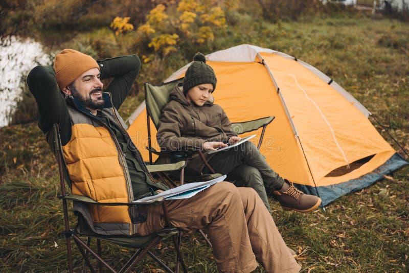 Sentada del padre y del hijo en la mirada del hijo de las sillas plegables imagen de archivo libre de regalías
