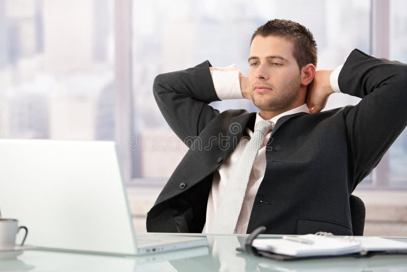 Sentada ejecutiva hermosa en estirar del escritorio imágenes de archivo libres de regalías