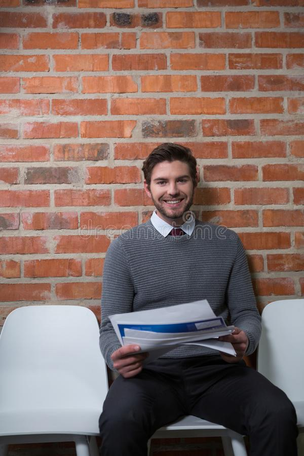 Sentada ejecutiva masculina con los documentos en zona de espera fotografía de archivo libre de regalías