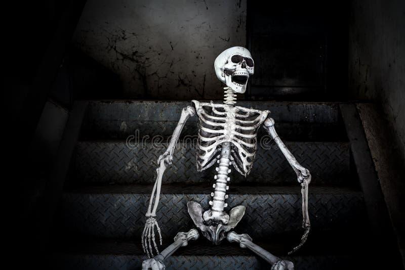 Sentada esquelética humana en las escaleras y risa, en el edificio abandonado asustadizo imagen de archivo