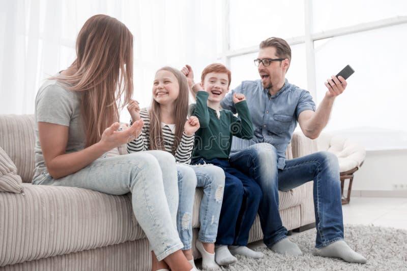 Sentada feliz de la familia que ve la TV en su hogar imagenes de archivo