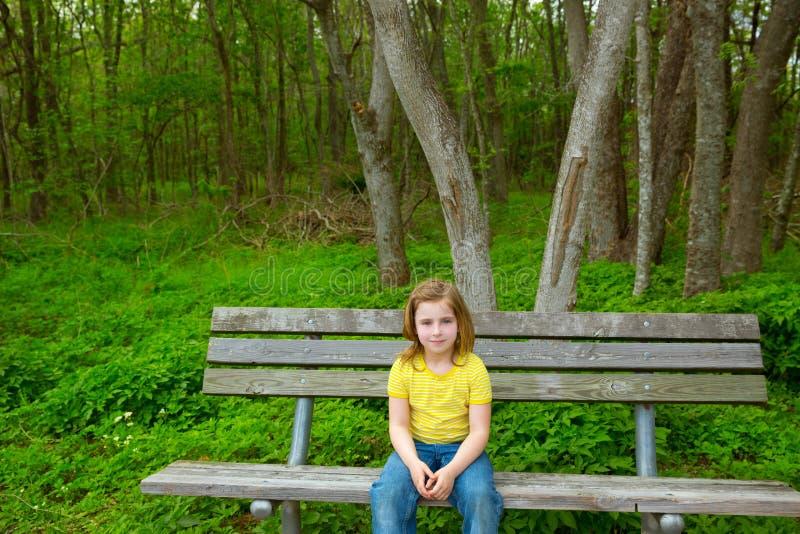 Sentada feliz de la muchacha sola de los niños en banco de parque imagenes de archivo