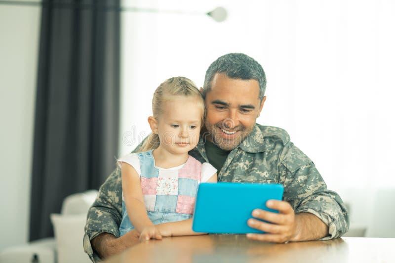 Sentada feliz de la sensación de la hija cerca del papá y de la historieta de observación foto de archivo libre de regalías