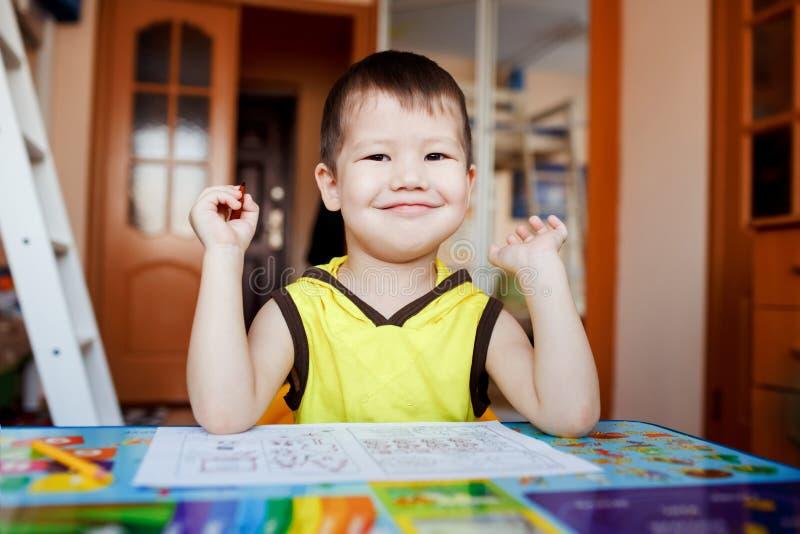 Sentada feliz del niño pequeño en la tabla después de dibujar, educación casera del preescolar imágenes de archivo libres de regalías