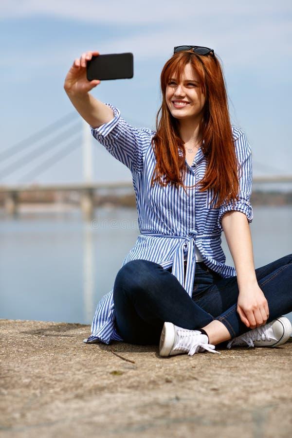 Sentada femenina en la arena por el río y el selfie de la fabricación imagen de archivo