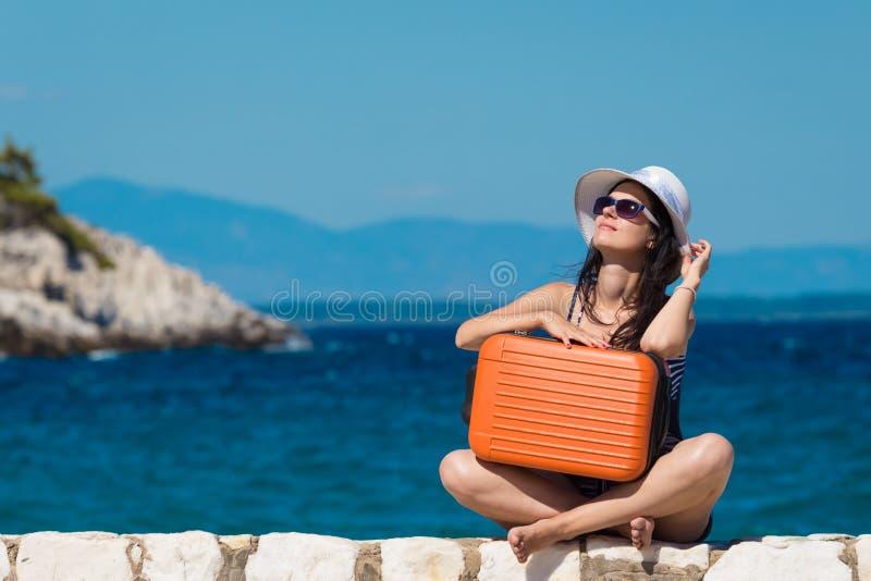 Sentada femenina en la pared de la playa y la maleta de la tenencia contra el mar azul fotos de archivo
