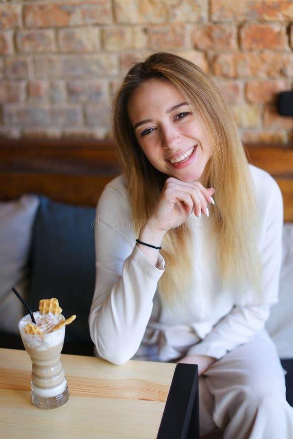 Sentada femenina en silla de madera cerca de la tabla con la taza de café y de presentación para la foto n fotografía de archivo libre de regalías