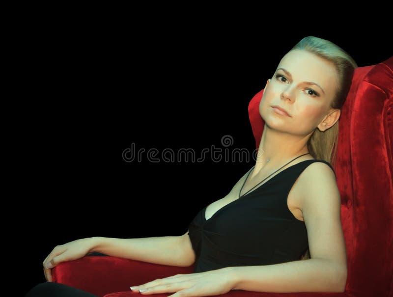 Sentada femenina en silla roja en la oscuridad fotos de archivo libres de regalías