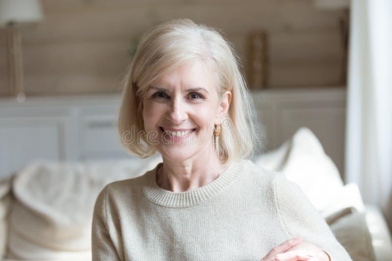 Sentada femenina envejecida sonriente en la sala de estar que mira la cámara fotografía de archivo