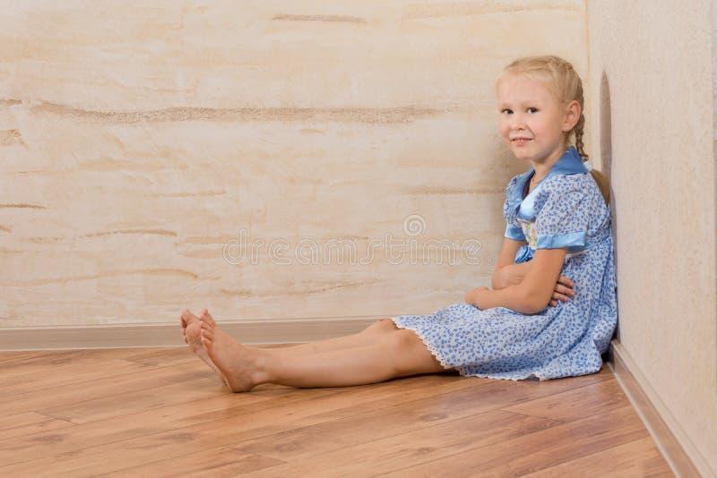 Sentada femenina hermosa joven en piso foto de archivo