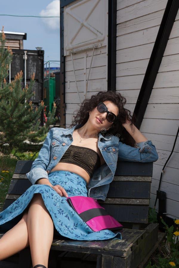 Sentada femenina joven en banco con las gafas de sol fotos de archivo libres de regalías