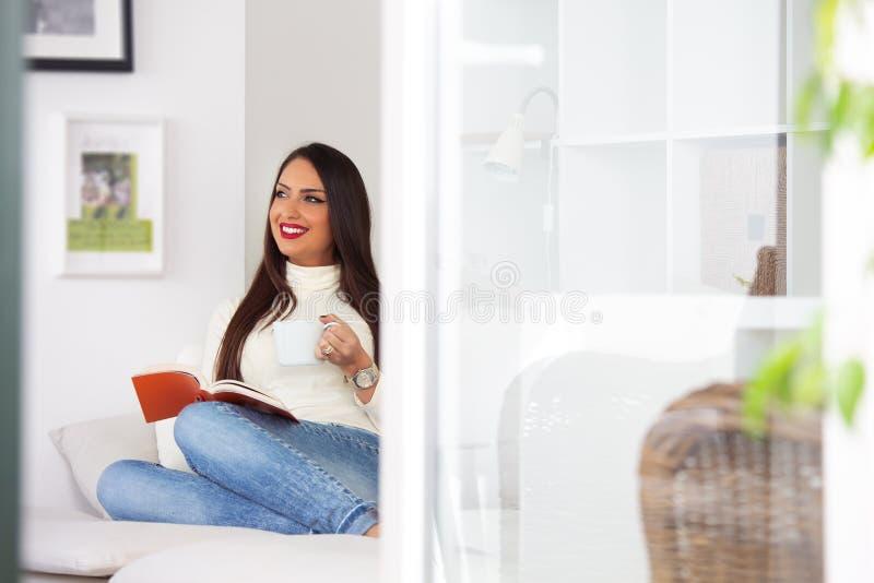 Sentada femenina joven hermosa en el sofá, leyendo un libro, sosteniendo una taza de té en su mano imágenes de archivo libres de regalías