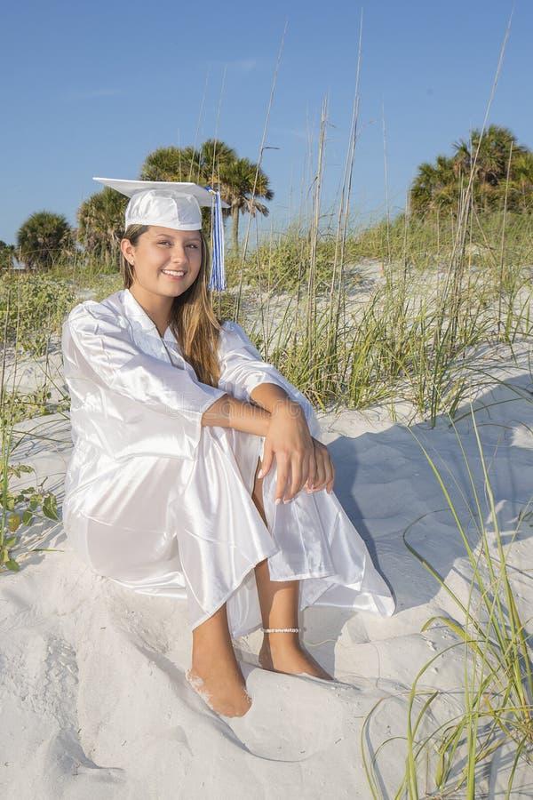 Sentada graduada de la hembra en una duna de arena imágenes de archivo libres de regalías