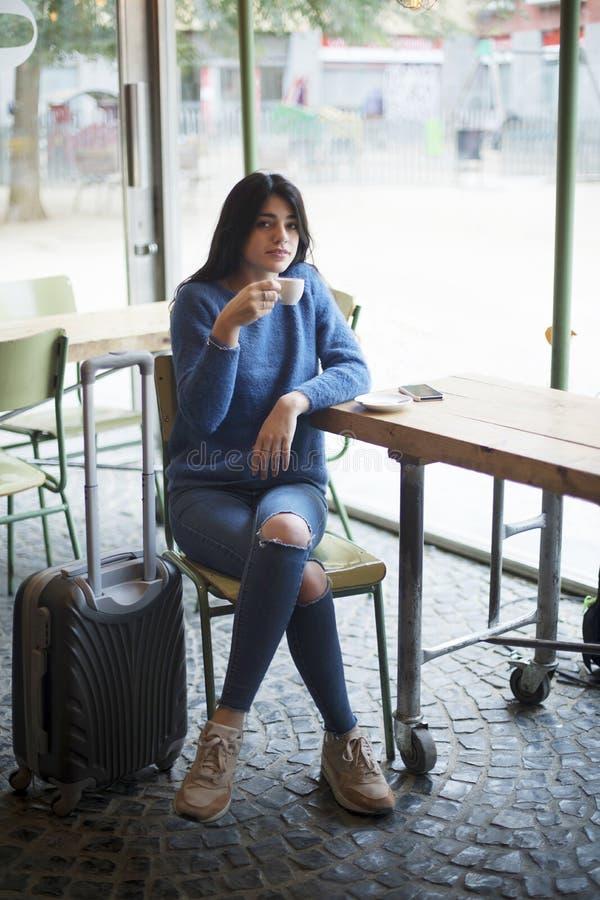 Sentada hermosa de la mujer joven mientras que bebe un café en un café foto de archivo