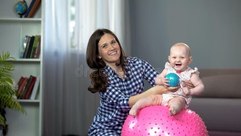 Sentada infantil adorable en bola y risa, bebé que se divierte con la madre cariñosa foto de archivo libre de regalías