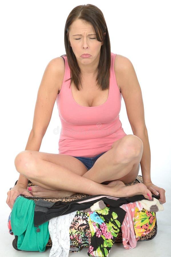 Sentada infeliz triste de la mujer joven cruzada Legged en una maleta que desborda foto de archivo libre de regalías