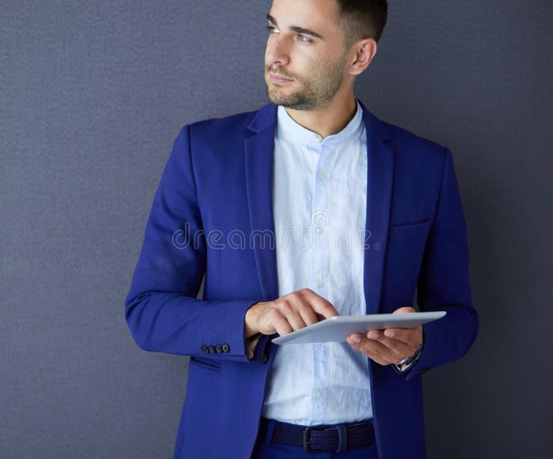 Sentada joven del hombre de negocios aislada en fondo gris fotografía de archivo libre de regalías