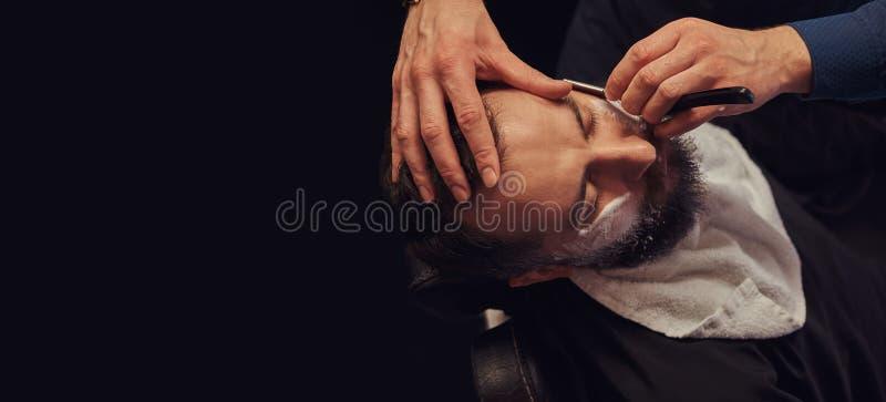 Sentada masculina barbuda en una butaca en una peluquería de caballeros mientras que el peluquero afeita su barba con una maquini foto de archivo libre de regalías