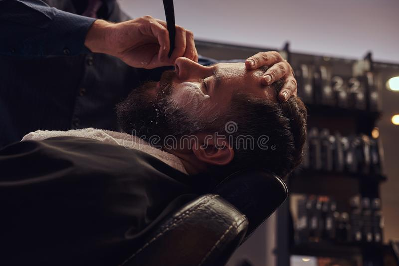 Sentada masculina barbuda en una butaca en una peluquería de caballeros mientras que el peluquero afeita su barba con una maquini imagen de archivo libre de regalías