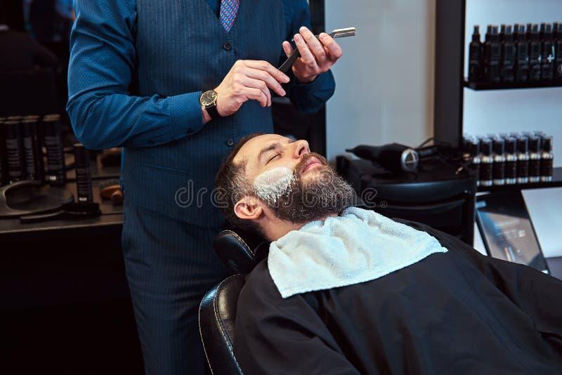 Sentada masculina barbuda en una butaca en una peluquería de caballeros mientras que el peluquero afeita su barba con una maquini imágenes de archivo libres de regalías