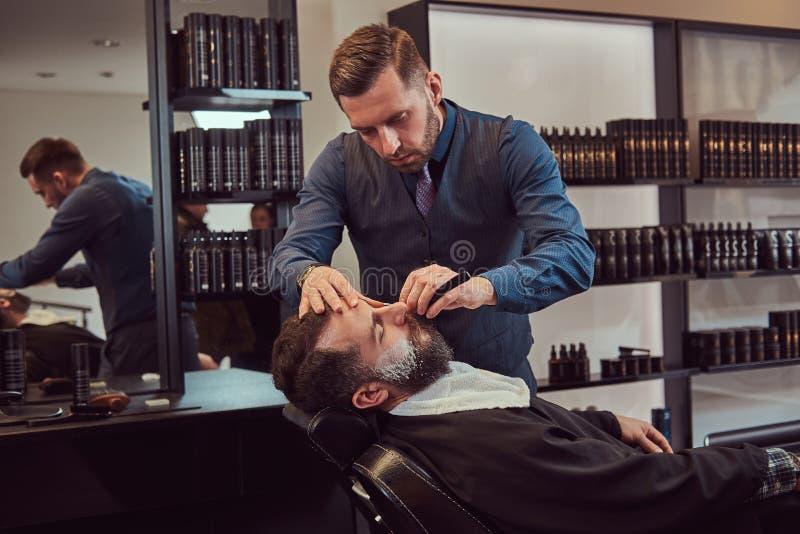 Sentada masculina barbuda en una butaca en una peluquería de caballeros mientras que el peluquero afeita su barba con una maquini imagenes de archivo