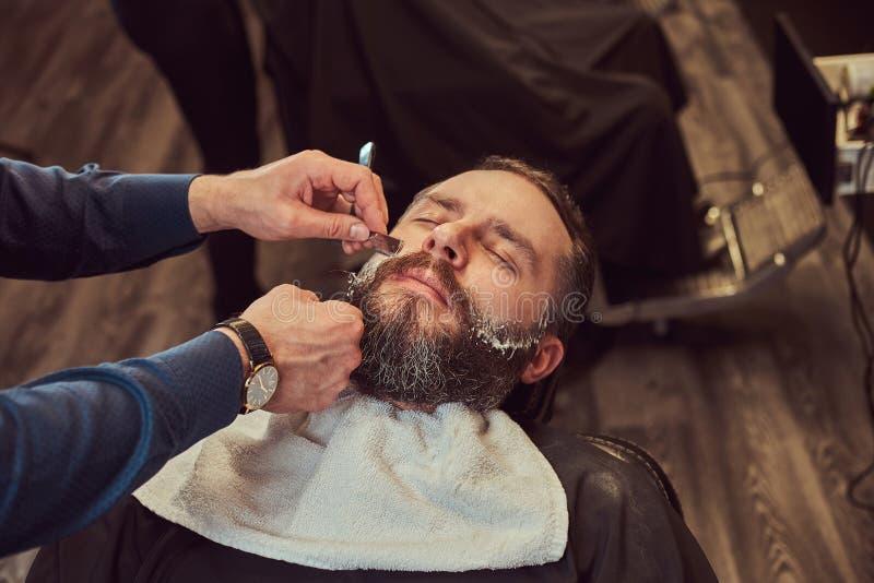 Sentada masculina barbuda en una butaca en una peluquería de caballeros mientras que el peluquero afeita su barba con una maquini fotos de archivo