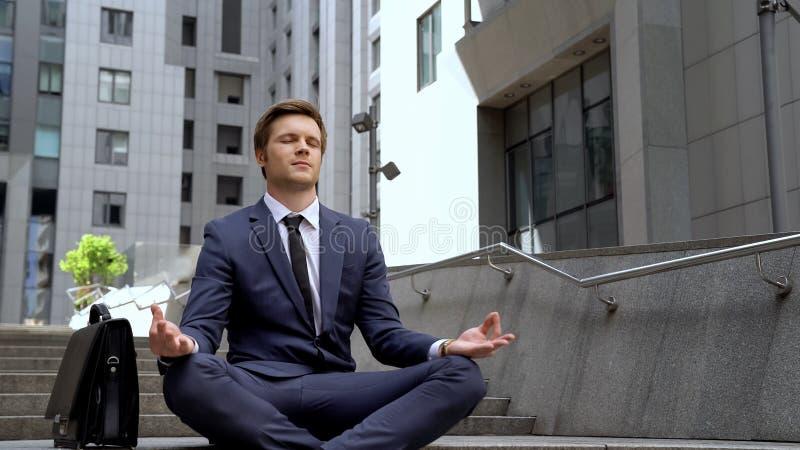 Sentada masculina hermosa en la posición de loto cerca del centro moderno de la oficina, calma foto de archivo libre de regalías
