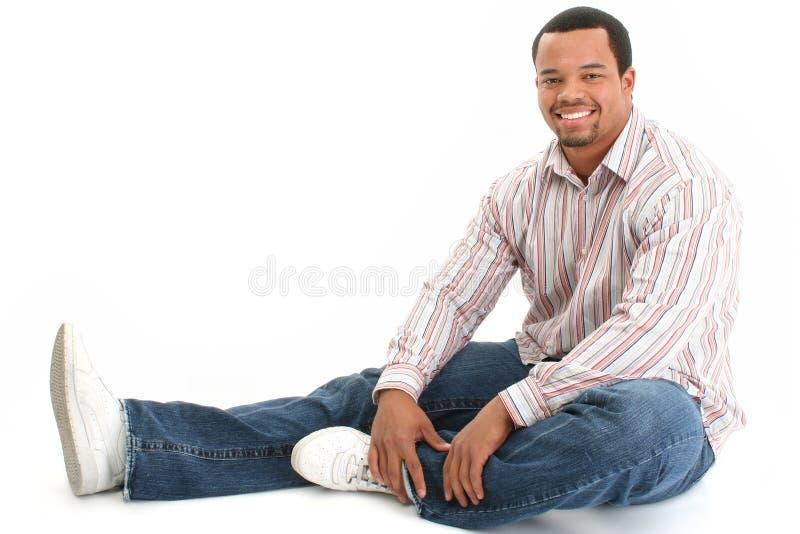 Sentada masculina hermosa en suelo fotografía de archivo
