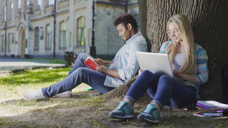 Sentada masculina joven debajo del árbol con el libro cerca de la hembra con el ordenador portátil, vida del estudiante fotografía de archivo libre de regalías