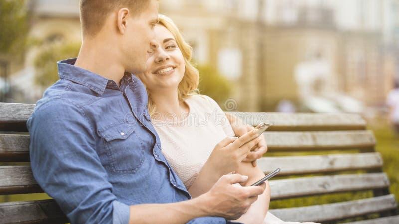Sentada masculina y femenina en banco con los teléfonos móviles, sonriendo y divirtiéndose imágenes de archivo libres de regalías