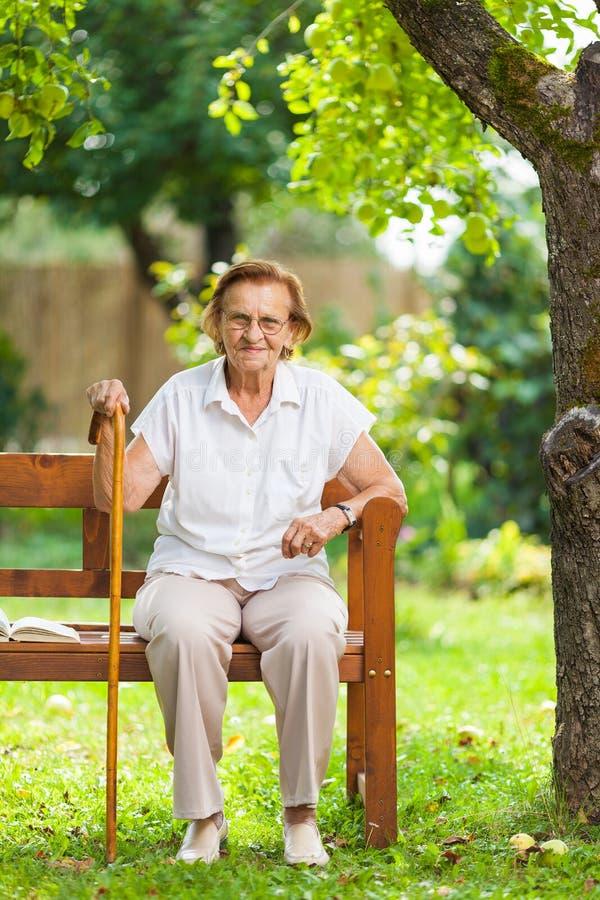 Sentada mayor de la mujer y relajación en un banco en parque fotografía de archivo libre de regalías