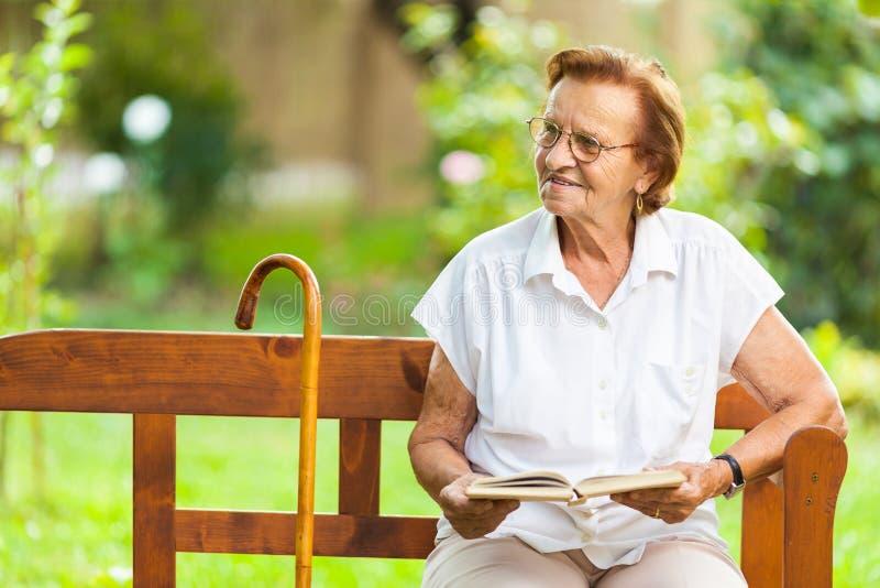 Sentada mayor de la mujer y relajación en un banco en parque fotografía de archivo
