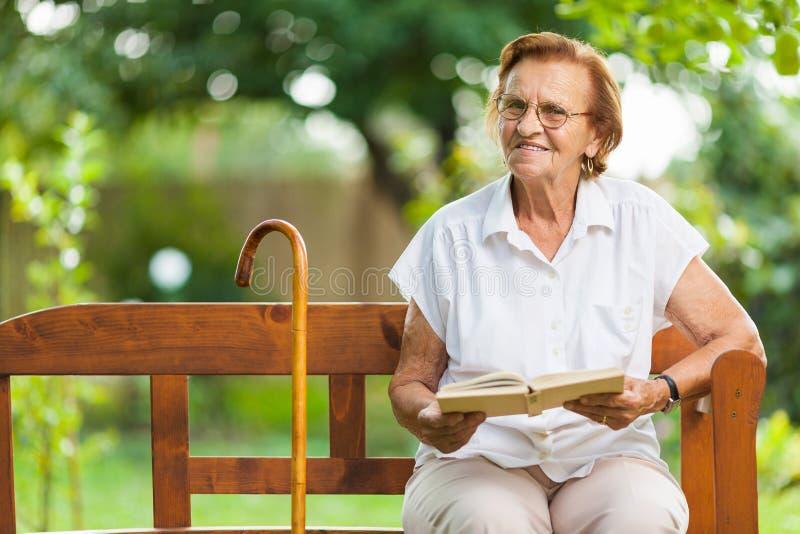 Sentada mayor de la mujer y relajación en un banco en parque fotos de archivo libres de regalías