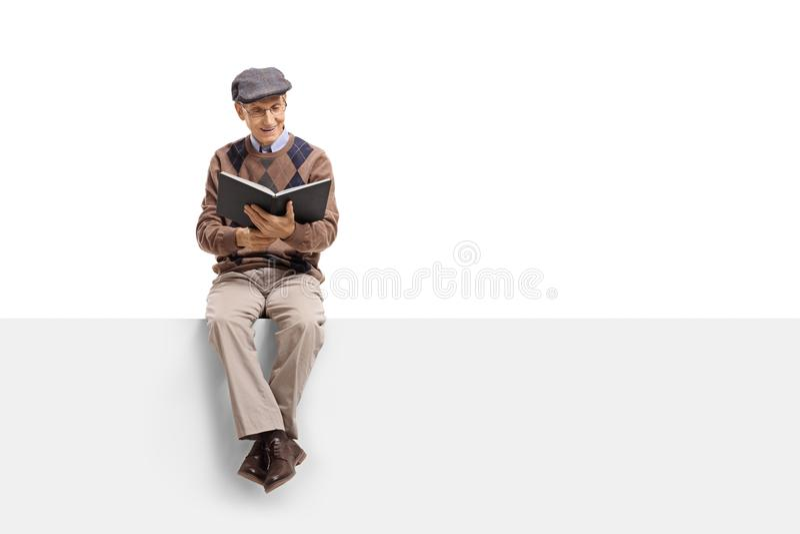 Sentada mayor en un panel y una lectura un libro fotos de archivo