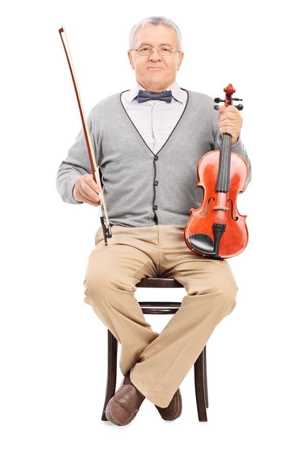 Sentada mayor en una silla y una tenencia un violín foto de archivo libre de regalías