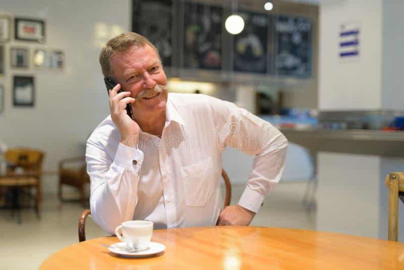 Sentada mayor feliz del hombre de negocios mientras que habla en el teléfono en la cafetería fotografía de archivo