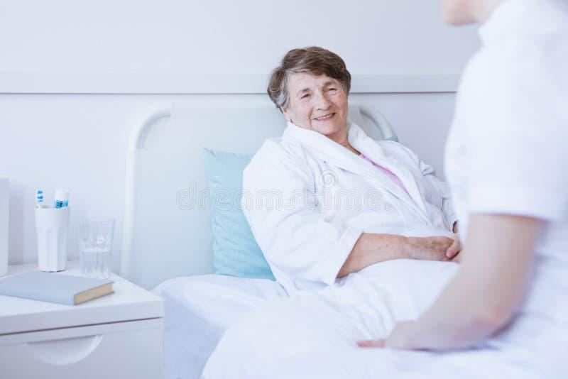 Sentada mayor sonriente en cama de hospital después de la cirugía fotos de archivo