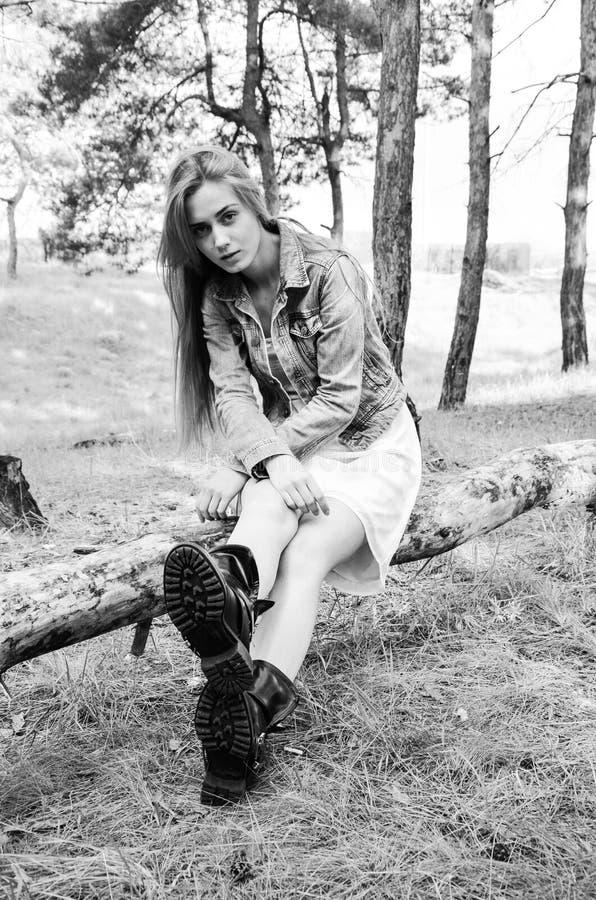 Sentada modelo atractiva en el registro de madera y mirada de la cámara con mirada del empollamiento fotografía de archivo libre de regalías