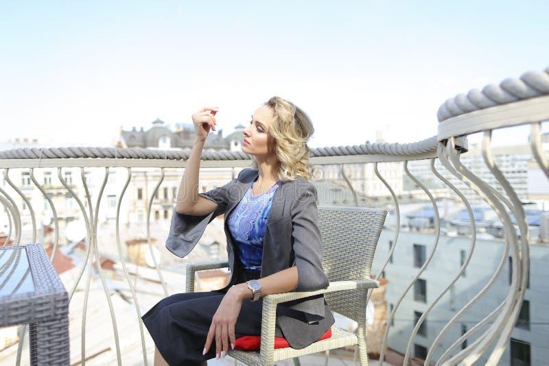 Sentada modelo de la foto femenina magnífica en el café en balcón con el fondo del paisaje urbano fotos de archivo
