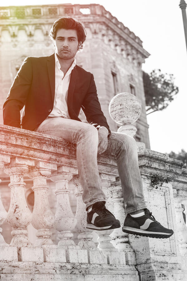 Sentada modelo del hombre elegante joven en la pared vieja del punto bajo histórico Ventanas viejas hermosas en Roma (Italia) imagen de archivo libre de regalías