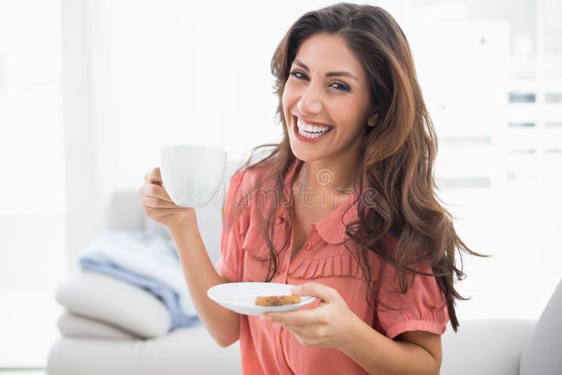 Sentada morena feliz en su sofá que sostiene la taza y el platillo fotografía de archivo libre de regalías