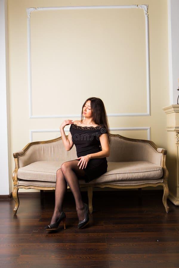 Sentada morena hermosa en el sofá foto de archivo