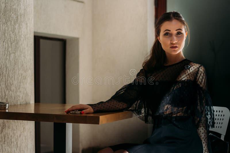 Sentada morena hermosa en una silla en una tabla Vestido negro con un platino y cuña en ella Esperar una reunión colocación imagenes de archivo