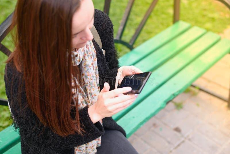 Sentada morena joven en un banco en el parque y las aplicaciones un smartphone visión superior, concepto de Internet, redes socia imagenes de archivo