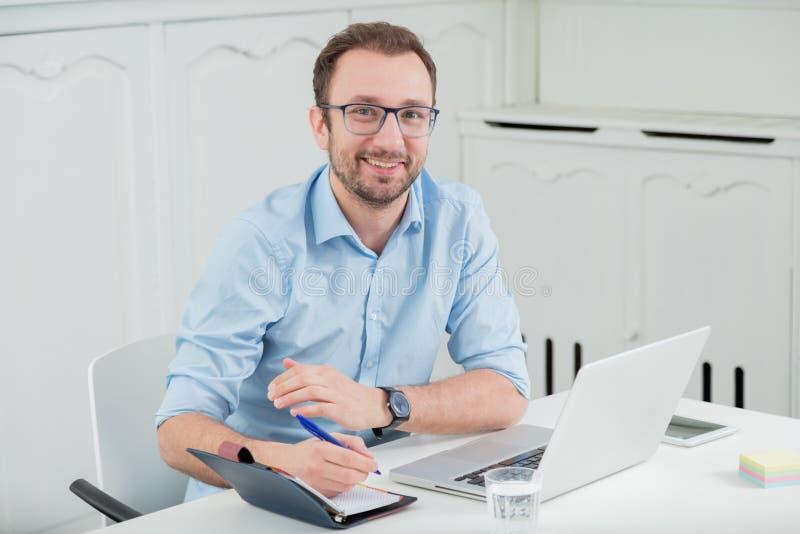 Sentada profesional masculina joven en el escritorio en la oficina foto de archivo