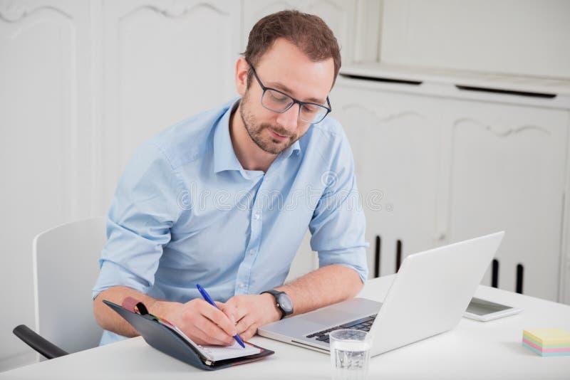 Sentada profesional masculina joven en el escritorio en la oficina y el wr imagen de archivo libre de regalías