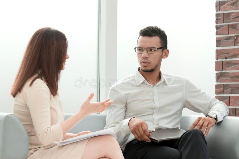 Sentada que habla del hombre de negocios y de la empresaria en el pasillo de la oficina foto de archivo libre de regalías