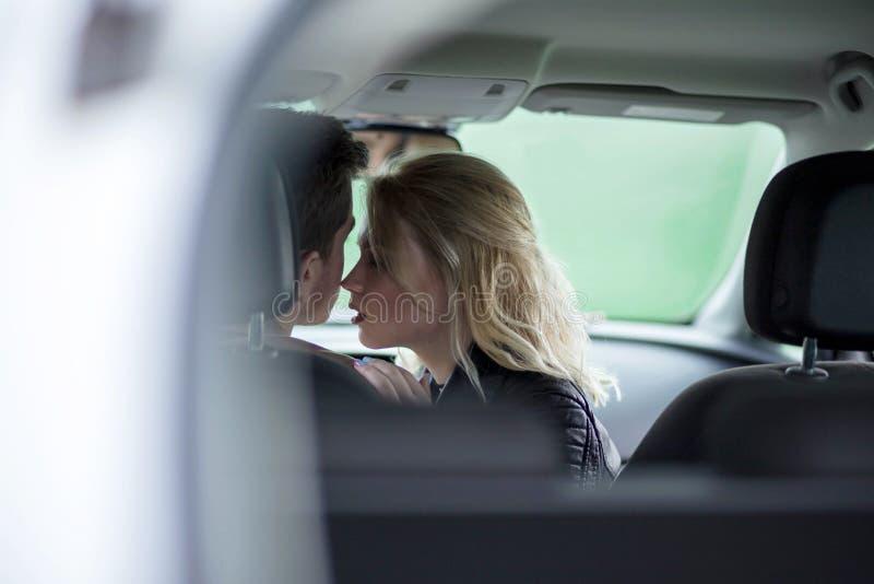 Sentada romántica de los pares jovenes en coche imagen de archivo libre de regalías