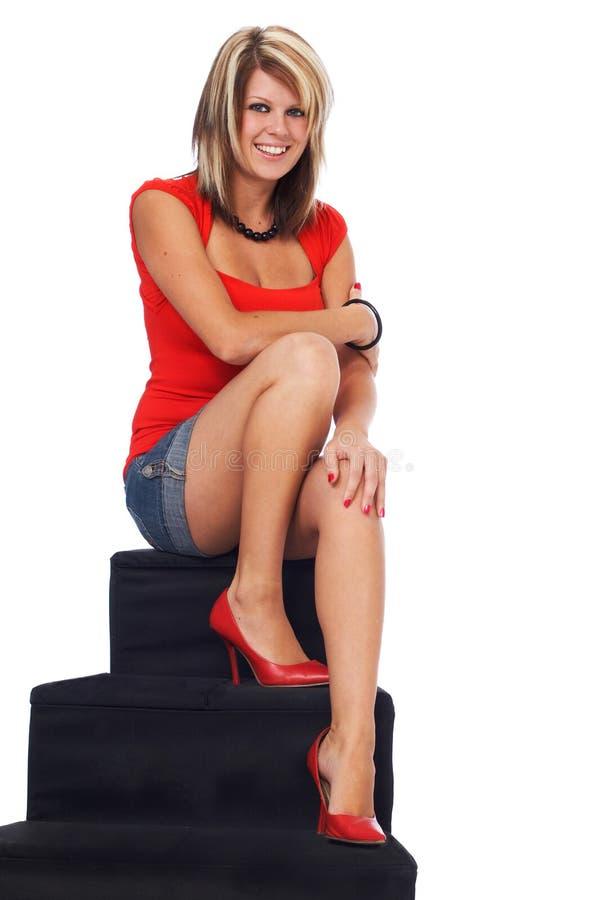 Sentada rubia feliz en las escaleras foto de archivo